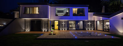 View of modern villa with pool in the night. Exteriors of modern luxury villa in the night stock images