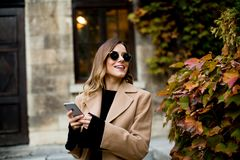 Modern woman using mobile phone at autumn outdoor Stock Images