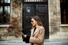 Modern woman using mobile phone at autumn outdoor Stock Image