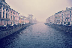 View of the Moika river with the Nevsky Prospekt in rainy cloudy. Day in Saint-Petersburg, Russia - vintage agede style Stock Photos