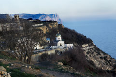 Monastery in mountains at the sea. View of a monastery, mountains and sea. Shortly before a decline. Horizontal photo Stock Images