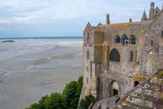 View of mont saint michel abbey with low tide. Partial view of mont saint michel abbey with low tide in a cloudy day; on the background there are the sign of royalty free stock photo