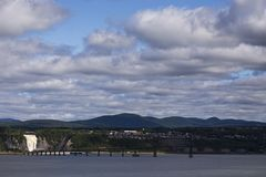 View of the Montmorency Falls and the Island of Orleans Bridge over the St. Lawrence River. With the Laurentian mountains in the background, Quebec, Canada stock photography