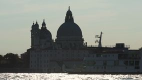View of monumental cathedral across river, cruise ship moving along Grand Canal. Stock footage stock video footage