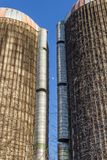 View of the moon between two tall grain silos with vines, blue sky royalty free stock photography
