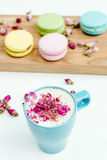 View on morning french macarons and a blue cappuccino cup with rose petals. On wood desk Royalty Free Stock Photo