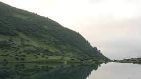 View of the morning lake and mountain in the Carpathians mountains stock video