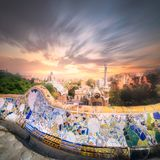 Barcelona cityscape in famous park Guell, Spain. View of mosaic tile and Barcelona cityscape in famous park Guell at summer sunset, Spain Stock Photos