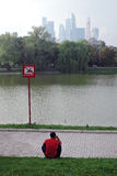 View of Moscow City Business Center. The Moscow river embankment. Autumn trees. Man sit by water. No swimming sign. Water reflection Stock Photography