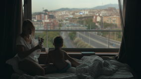 View of mother lying on the bed with small son against huge panoramic window and cityscape, Barcelona, Spain. View of mother sitting on the bed with small son stock video