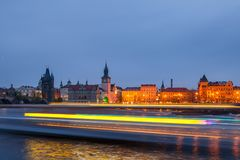 View of motion blurred lights of cruise ship in front of night old town of Prague and with reflection in Vltava River Stock Images