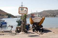 A view of a motorboat, and a motorbike passing by in the reflection of the street mirror against a sea backdrop in the lovely isla. Nd of Patmos, Greece in stock image
