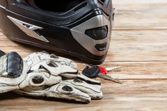 View of motorcycle rider accessories. Overhead view of biker accessories placed on rustic wooden table. Items included motorcycle helmet, gloves and keys Stock Photography