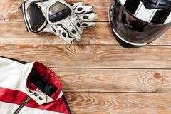 View of motorcycle rider accessories placed on rustic wooden tab. Overhead view of biker accessories placed on rustic wooden table. Items included motorcycle Stock Photo