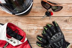View of motorcycle rider accessories placed on rustic wooden tab. Overhead view of biker accessories placed on rustic wooden table. Items included motorcycle Stock Image