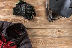 View of motorcycle rider accessories placed on rustic wooden tab. Overhead view of biker accessories placed on rustic wooden table. Items included motorcycle Royalty Free Stock Photo