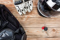 View of motorcycle rider accessories placed on rustic wooden tab. Overhead view of biker accessories placed on rustic wooden table. Items included motorcycle Royalty Free Stock Photos