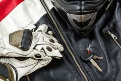 View of motorcycle rider accessories placed on rustic wooden tab. View of motorcycle rider accessories. Items included motorcycle helmet, gloves, keys and jacket stock photography