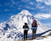 View of mount Dhaulagiri with two tourists. Great himalayan trail, Nepal royalty free stock photography