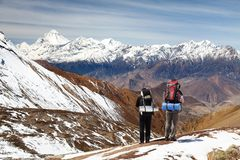 View of mount Dhaulagiri with two tourists. Great himalayan trail, Nepal Himalayas mountains stock photo