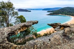 High view over ocean and beach through rocky outcrop. View from Mount Ettalong overlooking Pearl Beach and islands through rocky outcrop at Umina, Australia stock images