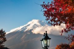 View Of Mount Fuji in autumn, Japan. View of Mount Fuji with cloud cover and a maple tree in autumn and a street lamp in the foreground from Fujikawagichiko, a stock photography