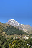 View of Mount Kazbek and Holy Trinity Church (Tsminda Sameba) near Gergeti village Royalty Free Stock Images