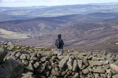 View from Mount Keen summit. Cairngorm Mountains, Aberdeenshire, Scotland. Hiker standing on the top of Mount Keen and looking at mountain view. Aberdeenshire royalty free stock image