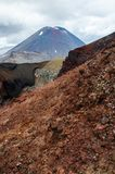 View of Mount Ngauruhoe - Mount Doom from Tongariro Alpine Crossing hike with clouds above and red crater in foreground.  stock photo