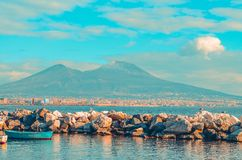 View of Mount Vesuvius and the Gulf of Naples with rocks and blue boat. Naples, Italy royalty free stock images