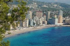 View from the mountain Ifach in Spain to the sea town of Calpe with the beach and high houses, the clear blue sea under your feet.  stock photography