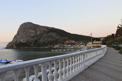 View of the mountain Koba-Kaya from the seaside promenade in th. View of the mountain Koba-Kaya from the seaside promenade with a white balustrade in the morning royalty free stock photo