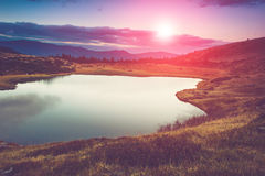 View of the mountain lake in evening. View of the mountain lake. Fantastic evening glowing by sunlight Royalty Free Stock Photography