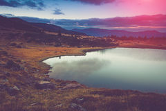 View of the mountain lake. Fantastic evening glowing by sunlight Royalty Free Stock Images