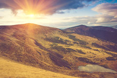 View of mountain lake with sunlight. Filtered image:cross processed vintage effect Stock Photography