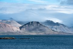 Mountain peaks at the west coastline of Iceland. View of mountain peaks at the west coastline of Iceland, surrounded by white clouds royalty free stock photos