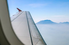 View of mountain peaks and wings of the aircraft from inside Royalty Free Stock Photo