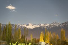 A view of Mountain and pine trees with snow on top at night time in Leh, Ladakh, India stock image