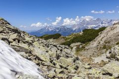 View from mountain Rippetegg with some snow to distant Dachstein. View from mountain Rippetegg with some snow and rocks to distant mountain Dachstein in Austria Stock Images