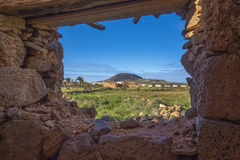 View of mountain through ruin in La Oliva Fuerteventura Las Palmas Canary Islands Spain. View of mountain and a field through ruin in La Oliva Fuerteventura Las Royalty Free Stock Photo