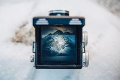 View on the mountain scenery through the viewfinder of the old camera photo. Photographer of the old school takes on a stock photography
