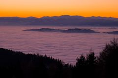 View from mountain Schoeckl over low stratus to Pack, sunset. View from mountain Schoeckl over low stratus to mountain range Pack with Speikkogel and Stock Photography