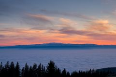View from mountain Schoeckl over low stratus to beautiful sunset. View from mountain Schoeckl in Styria over low stratus to mountain ranges Koralpe and Pack to Royalty Free Stock Images