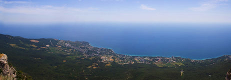 View from the mountain to the seashore. Stitched Panorama. The horizon line between sea and sky Royalty Free Stock Image
