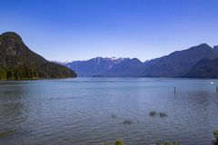 A view of the mountains  across a bay. With blue sky in the background british columbia lake landscape nature outdoor scenery summer water royalty free stock image