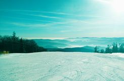 Snowy ski hill with blue sky stock images