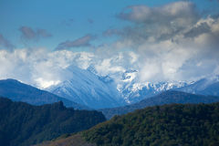 View of the mountains in the clouds. View of the mountains with snowy peaks in the clouds Royalty Free Stock Images
