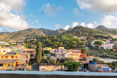 View of mountains, country houses, trees under blue cloudy sky. At early sunset in mediterranean marine town in Sicily Italy Stock Image