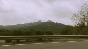 View at mountains full of green trees and plants from motorway. Castle on other side. Journey stock video