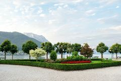 View of the mountains, the lake and the embankment of the city with trimmed trees, shrubs and flower beds royalty free stock photography